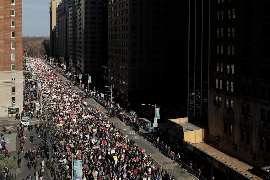 """Protesters took to the streets of New York City (left) and elsewhere in the world, for a second Women's March on Saturday, one year after President Donald Trump's inauguration. Carrying anti-Trump placards with messages such as """"Fight like a girl"""" an"""