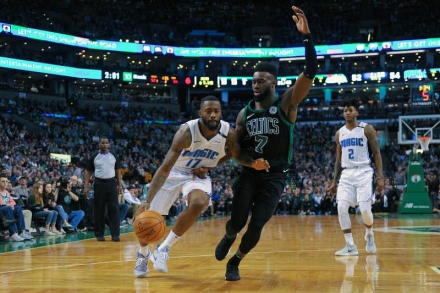 Orlando Magic forward Jonathon Simmons controls the ball while Boston Celtics guard Jaylen Brown defends during the first half of the match.