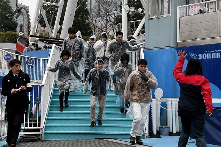 An amusement park worker (right) directing visitors during a simulated emergency in the event of a ballistic missile launch at the Tokyo Dome on Jan 22, 2018.