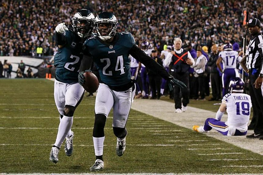 The Eagles' Malcolm Jenkins (left) and Corey Graham (centre) celebrate an interception as the Vikings' Adam Thieler (right) sits on the ground in the second half of the NFC Championship game between the Minnesota Vikings and the Philadelphia Eagles o