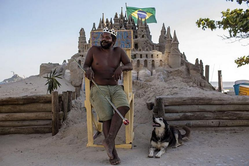 With a crown on his head, Marcio Mizael Matolias sits next to his dog, Humana, on a throne in front of his sand castle on a sunny summer afternoon on the beach of Barra da Tijuca in Rio de Janeiro, Brazil, on Jan 18, 2018.