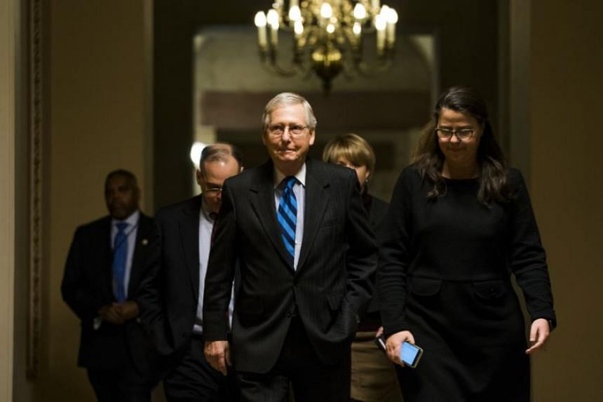 Republican Senate Majority Leader from Kentucky Mitch McConnell (centre) walks to the Senate floor to make an announcement as the Senate continues work on ending the government shutdown in the US Capitol in Washington, DC on Jan 21, 2018.