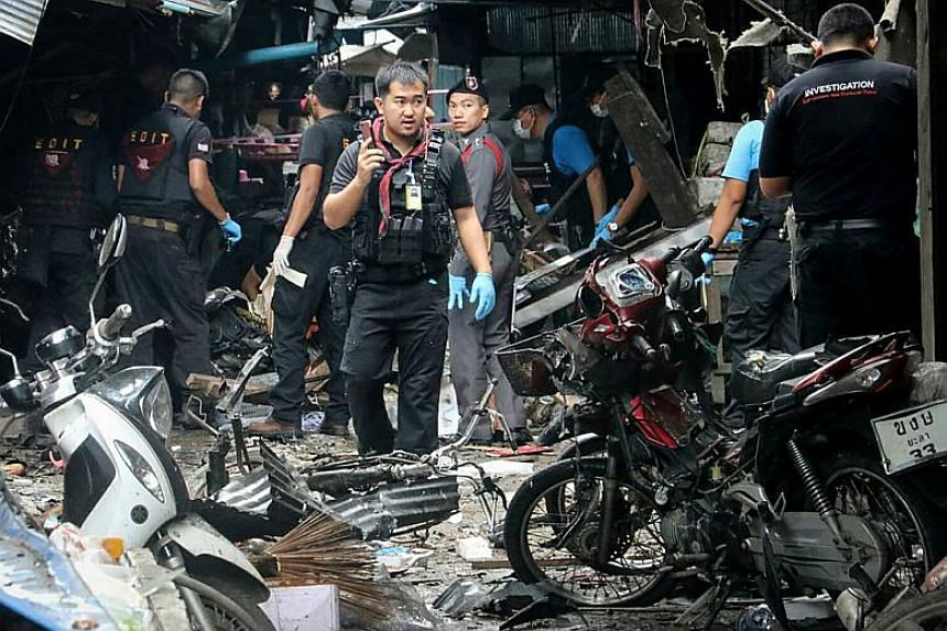 A Thai forensics unit scours the aftermath of a motorcycle bombing which killed three civilians and wounded others at a market in the restive southern Thai province of Yala on Jan 22, 2018.