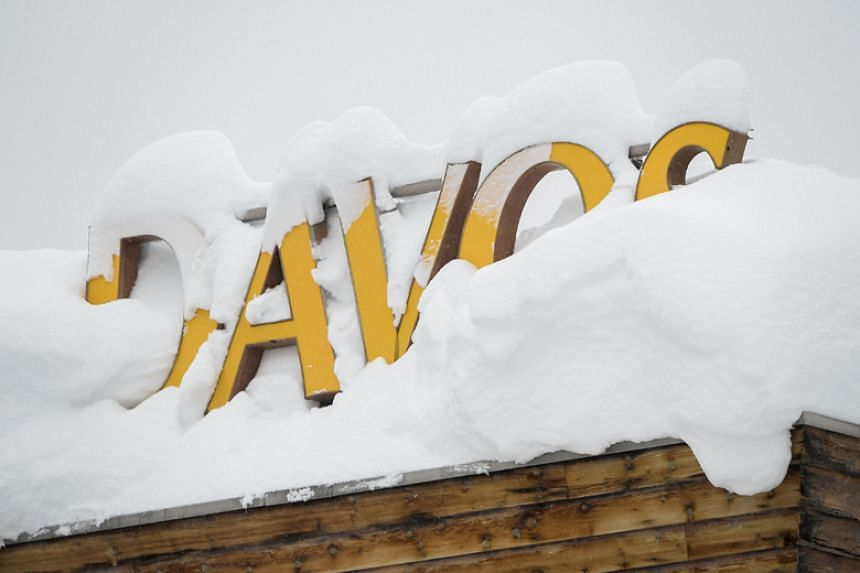"Letters reading ""Davos"" are covered in snow on the rooftop of a hotel, near the Congress Centre ahead of the opening of the 2018 World Economic Forum annual summit in in the Swiss Alps on Jan 22."