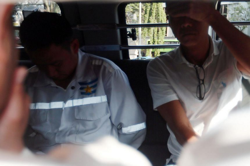Two of the 11 suspects involved in the theft of fuel from Shell being escorted in police vehicles, on Jan 9, 2018.
