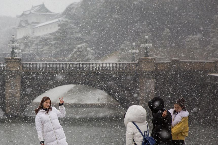 Tourists posing in the snow in front of the Imperial Palace in Tokyo, on Jan 22, 2018.