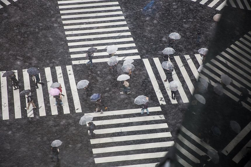 Pedestrians crossing a street during a snowstorm in central Tokyo on Jan 22, 2018.