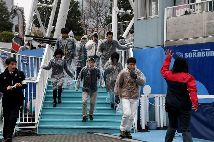 An amusement park worker (right) directs visitors during a simulated emergency in the event of a ballistic missile launch, at an amusement park near Tokyo Dome stadium in Tokyo, Japan, on Jan 22, 2018.