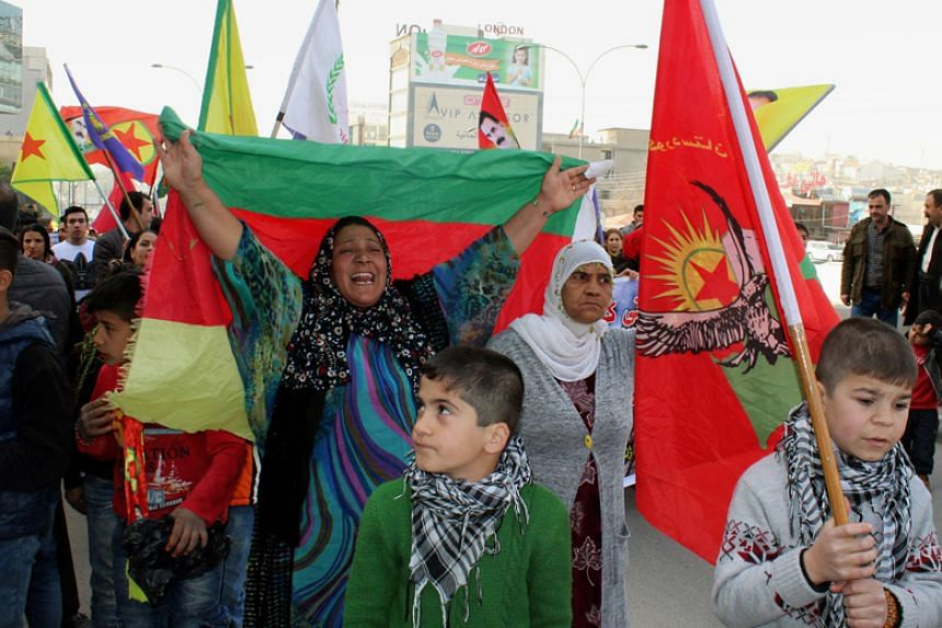 Syrian Kurdish refugees carry the Kurdish YPG forces flag during a demonstration against the military operation by the Turkish army against the Kurdish YPG forces in Syria's Afrin, in Sulaymaniya, Iraq, on Jan 21.