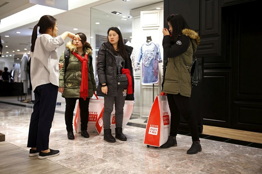 Chinese tourists ask a sales assistant for directions at a Lotte department store in Seoul on Feb 2, 2016.