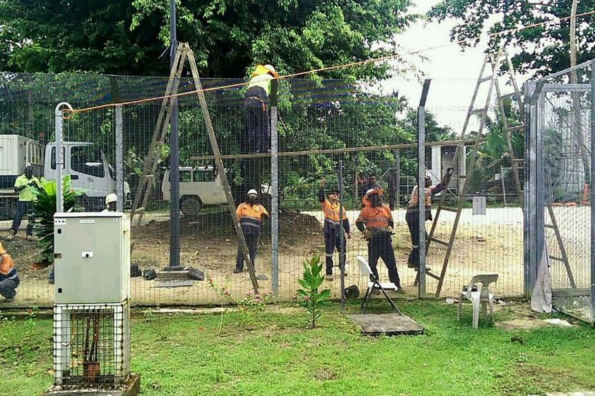 Contractors dismantling fences at the Australian detention centre on Manus Island in Paupa New Guinea on Nov 9, 2017.