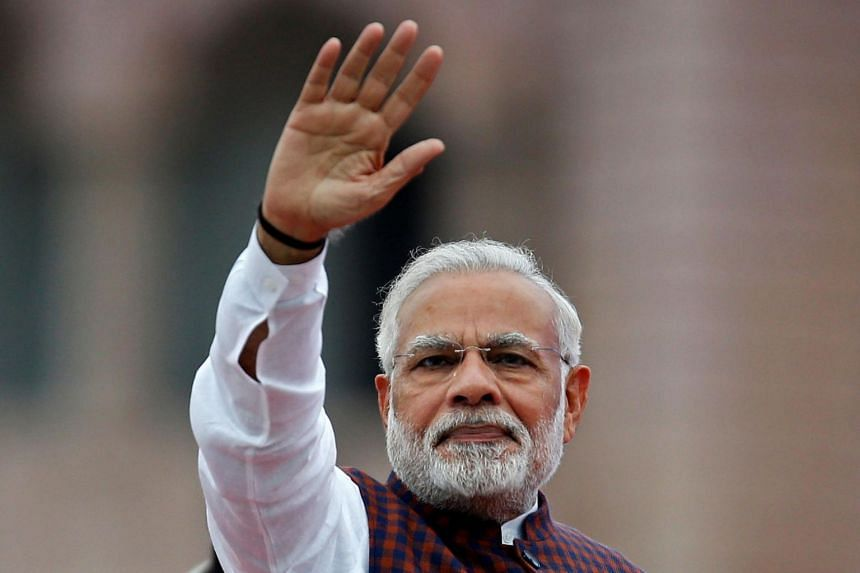 India's Prime Minister Narendra Modi waves to his supporters as he arrives to address them during an election campaign meeting ahead of the Gujarat state assembly elections on Dec 3, 2017.