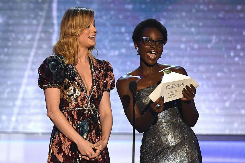 Actresses Brie Larson (far left) and Lupita Nyong'o presenting the award for outstanding performance by a cast in a motion picture during the 24th Annual Screen Actors Guild Awards show. Frances McDormand, arms outstretched, celebrates with the cast