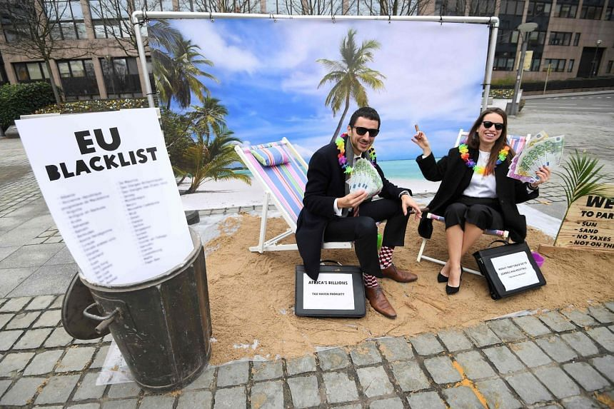 Oxfam activists staging a satirical play about tax havens, in Brussels on Dec 5, 2017. The EU removed eight countries from their tax haven blacklist on Jan 23, 2018, after the countries said they would address the concerns.
