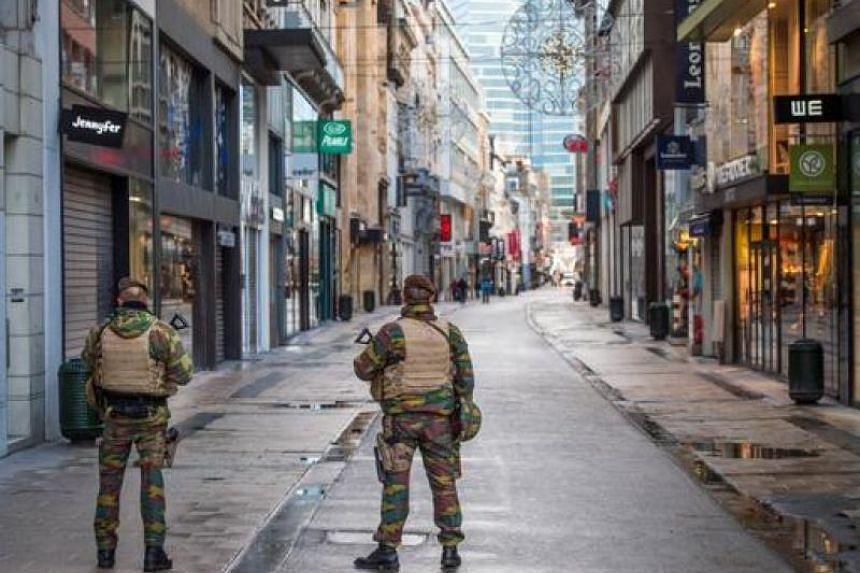 Belgian soldiers patrol in Rue Neuve, the busiest shopping street in Brussels, on Nov 22, 2015.