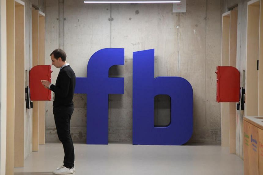 A man waits for an elevator in front of a logo at Facebook's headquarters in London, Britain, on Dec 4, 2017.