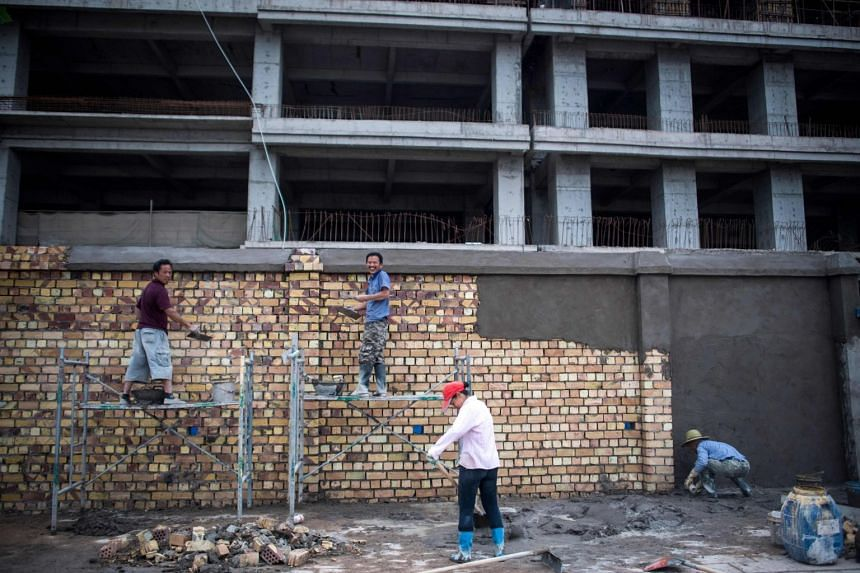 Workers plastering a brick wall in front of a construction site in a development called 'Shenzhen City' on the outskirts of Kashgar in China's western Xinjiang province.