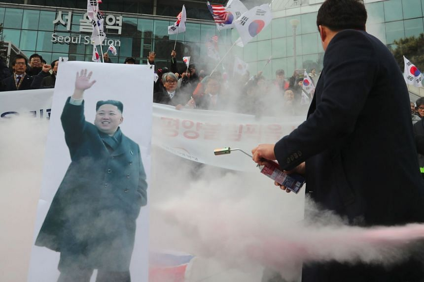 Protestors try to burn a picture of Kim Jong Un during an anti-North Korea rally in Seoul, South Korea, on Jan 22, 2018.