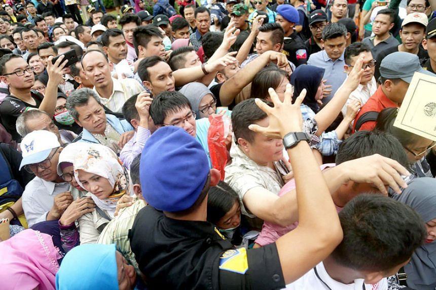 Hundreds of people jostle to process their passports during the 2018 Immigration Festival at National Monument park in Jakarta on Jan 21.