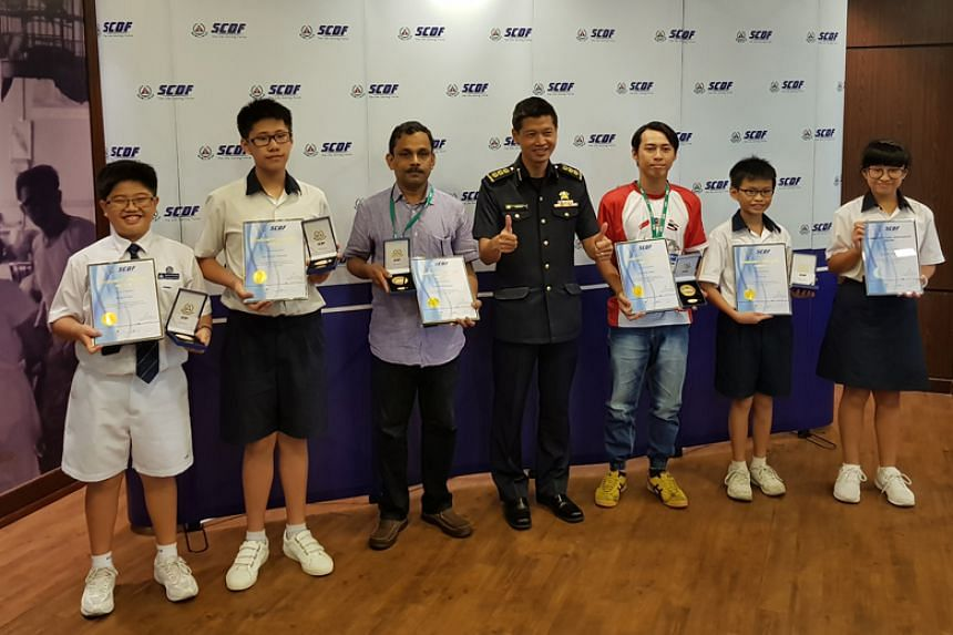 Receiving their awards from the 2nd Singapore Civil Defence Force Division Alan Toh (fourth from left) were (from left) Branson Ong, 12; Jose Antonio Alexander, 12; Govindan Meyyappan, 49; Huang Han Xiang, 29; Lin Yu Jie, 12; and Megan Seow, 12.