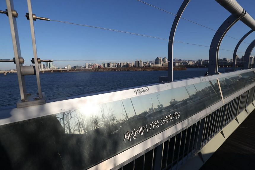 """A banner with a message reading """"You are the most valuable person in the world"""" is attached to a barrier designed to make suicide more difficult on Mapo Bridge, a well-known suicide spot, in Seoul."""