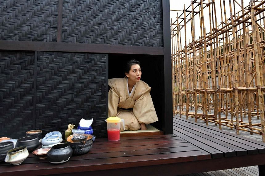 Japanese tea ceremony performance artist Mai Ueda looking out from a wooden tea house, part of a bamboo maze installation display by artist Rirkrit Tiravanija, on the roof of the National Gallery Singapore.