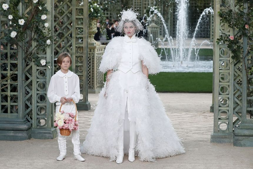 US model Brad Kroenig's son Hudson and a model present creations from the Chanel Spring/Summer 2018 Haute Couture collection.