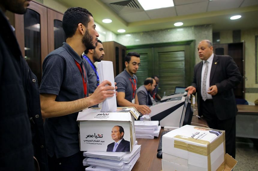 Members of Sisi's presidential campaign count boxes containing his candidacy papers.