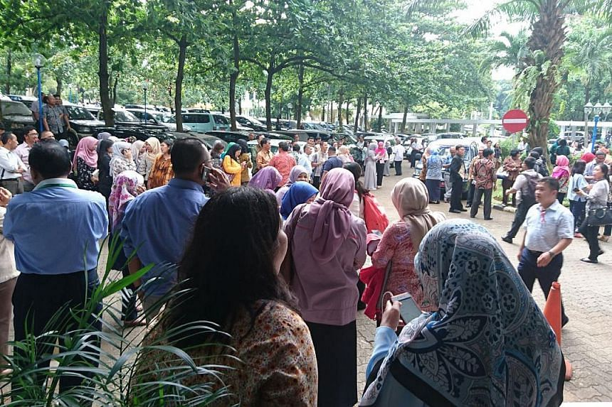 Office workers being evacuated from the Ministry of Agriculture in Jakarta. Offices and high-rise homes in the city were quickly evacuated as the quake and its aftershocks shook buildings. In Banten and West Java provinces, 479 houses were damaged, b