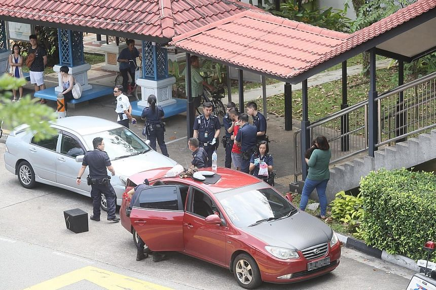 Above: Police at the scene in Bishan with the two cars on Monday morning. Left: The 24-year-old woman under arrest for drug-related offences.