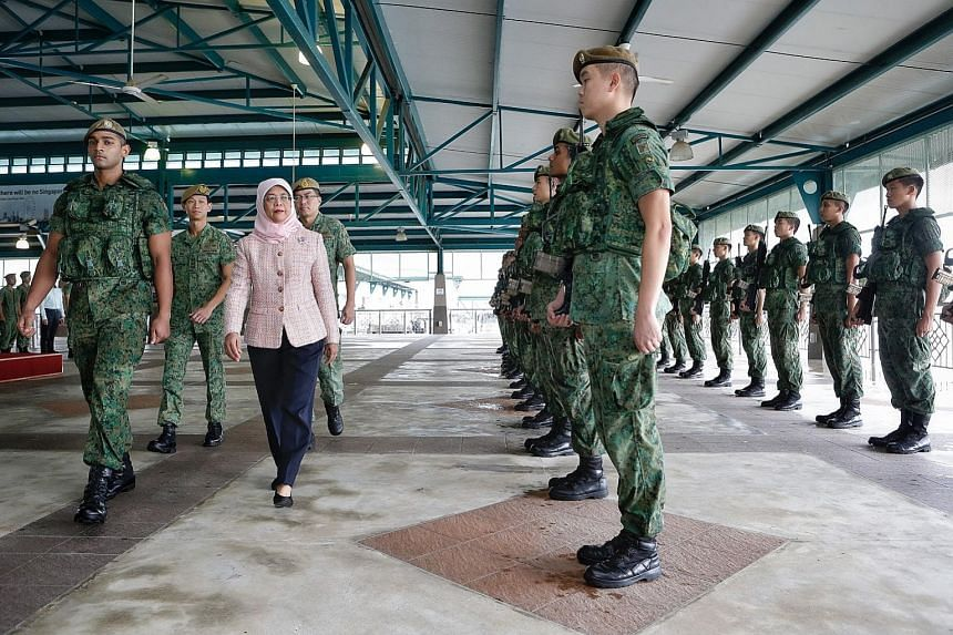 President Halimah Yacob inspecting the welcome guard on her first visit to an SAF unit at the Basic Military Training Centre on Pulau Tekong yesterday. She was accompanied by BMTC Commander Colonel Patrick Ong (second from left)) and Chief of Army, M