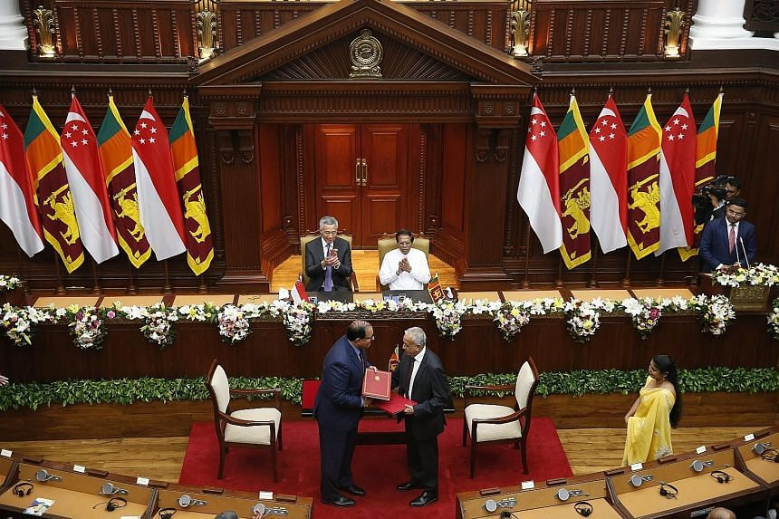 Prime Minister Lee Hsien Loong and Sri Lankan President Maithripala Sirisena witnessing the signing of the FTA yesterday between Minister of Trade and Industry (Industry) S. Iswaran and Sri Lankan Minister for Development Strategies and International