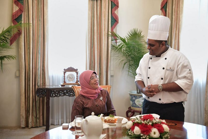 President Halimah Yacob speaking with Mr Paul Simon before tucking into the three-course meal he prepared for her at the Istana, on Jan 24, 2018.