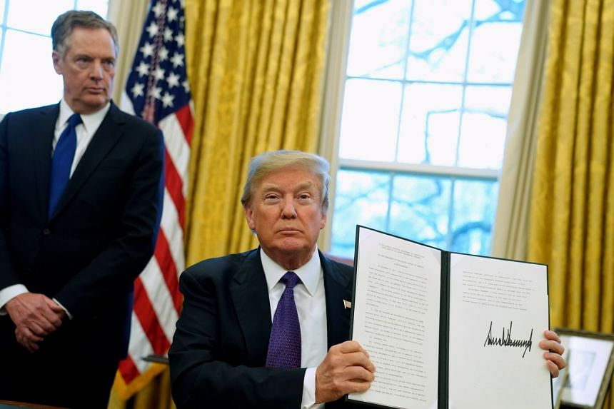 US President Donald Trump, flanked by US Trade Representative Robert Lighthizer, holds up a directive to impose tariffs on imported washing machines.