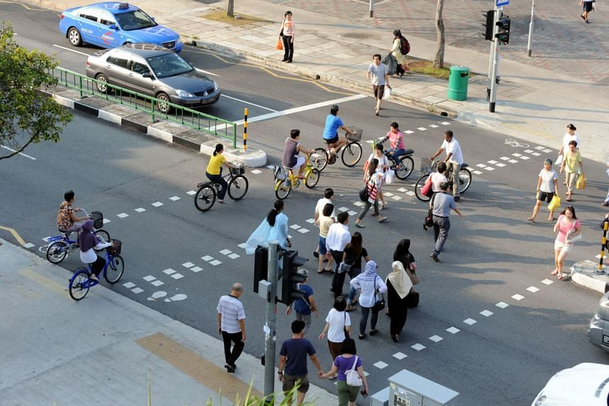 Cyclists and pedestrians crossing a road junction at Tampines Avenue 3.