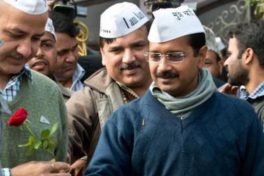 Aam Admi Party (AAP) leader Arvind Kejriwal receives a rose as he arrives to address a press conference at the party headquarters in Ghaziabad, on the outskirts of New Delhi, on Dec 23, 2013.