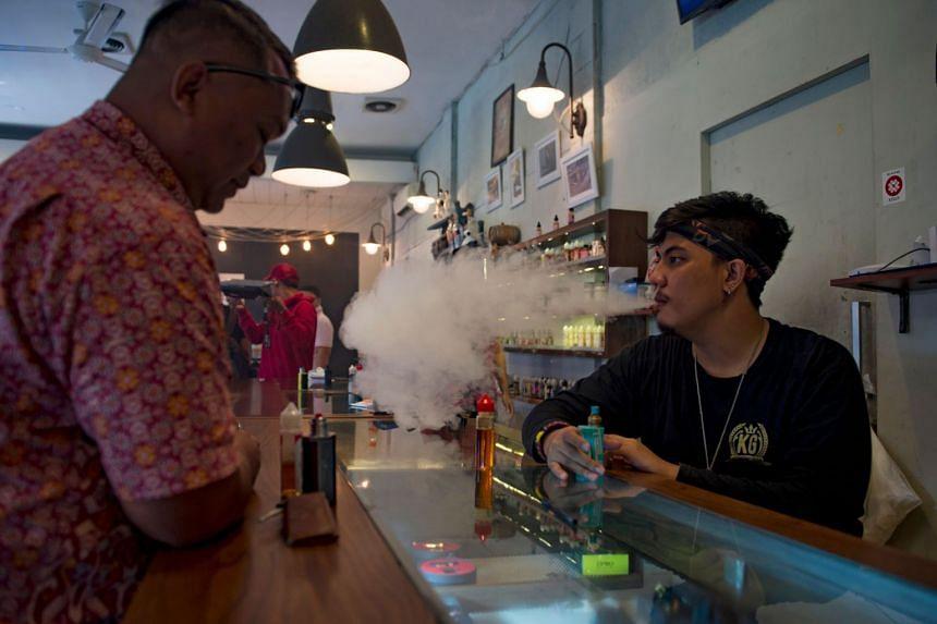 An e-cigarette cafe employee (right) vaping beside a customer in Jakarta.