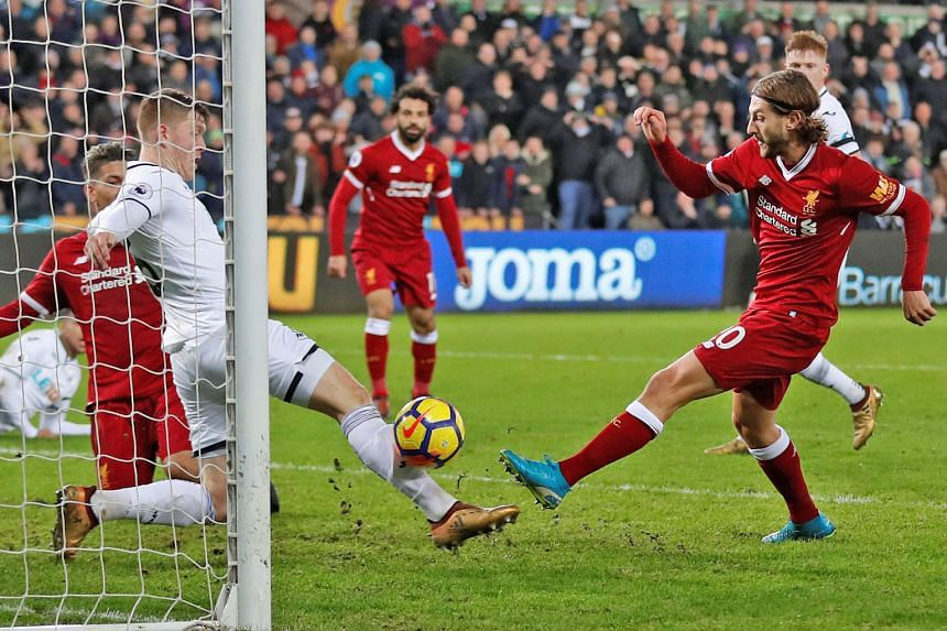 Liverpool's Adam Lallana (far right) misses a chance to equalise deep into stoppage time as Alfie Mawson blocks his shot. The 1-0 defeat by Swansea on Monday was only the Reds' third league loss this season and came after beating EPL leaders Manchest