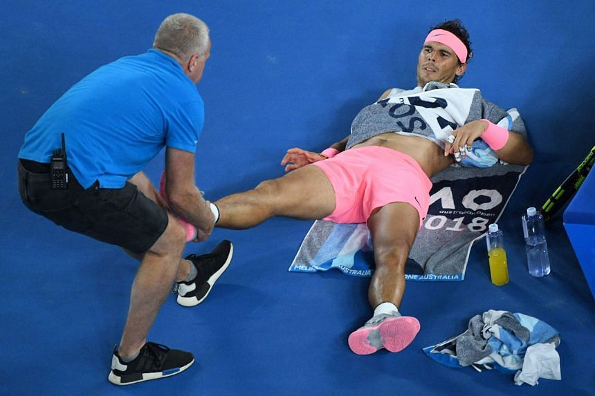 World No. 1 Rafael Nadal receiving medical attention during his quarter-final match against Croatia's Marin Cilic in Melbourne yesterday before the Spaniard retired after trailing 0-2 in the fifth set.