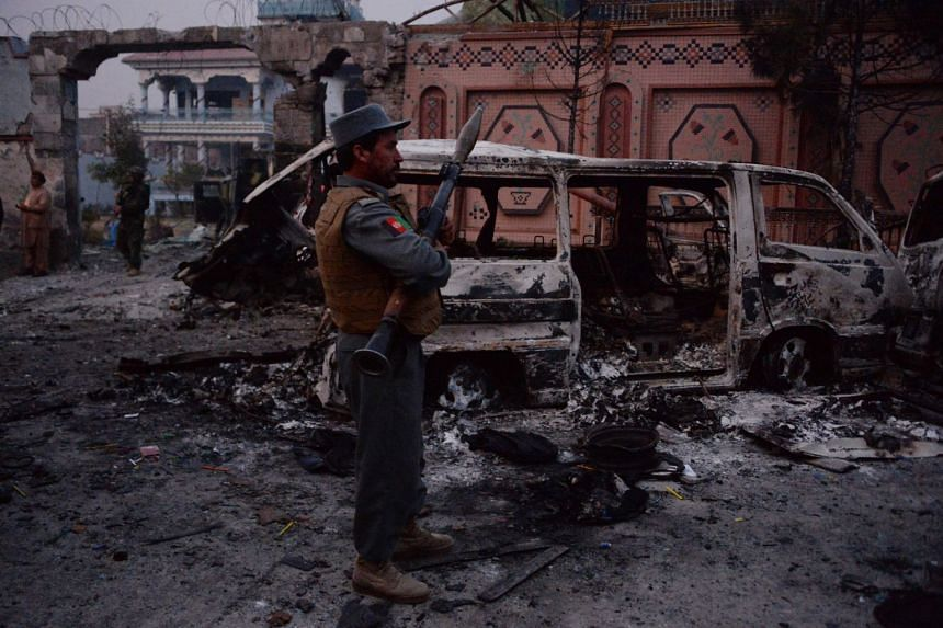 Afghan security forces inspect the site of the attack on British charity Save the Children in Jalalabad.