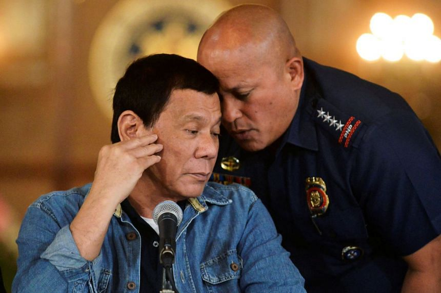 Philippine National Police chief General Ronald Dela Rosa whispers to President Rodrigo Duterte during the announcement of the disbandment of police operations against illegal drugs at the Malacanang palace in Manila, Philippines on Jan 29, 2017.
