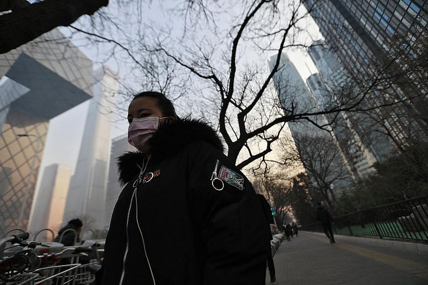 A woman wearing a mask as protection against the smog in Beijing earlier this month. Though China's capital has made progress in cutting breathable particulate matter, the level has yet to reach the official standard.