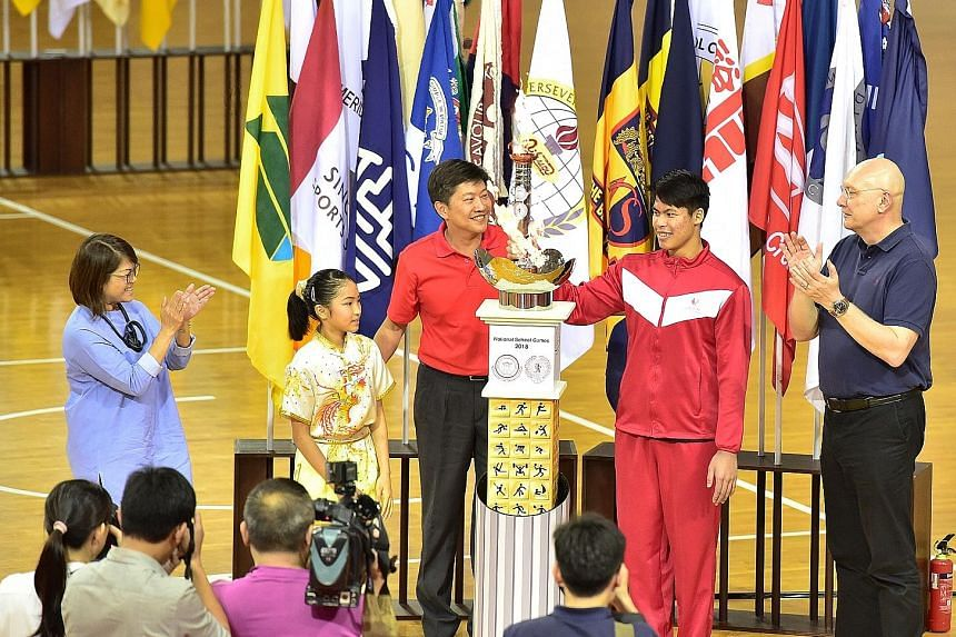 Torch bearer Lincoln Forest Liqht Man, an 18-year-old Singapore Sports School student, lighting the cauldron at the opening of the National School Games yesterday with fellow torch bearer Cassandra Ong, an 11-year-old Tao Nan School pupil. With them