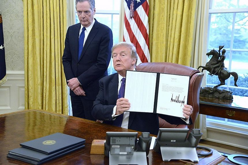 US President Donald Trump displaying the executive order after signing it at the White House on Tuesday. China's reaction has been cautious, with the Commerce Ministry suggesting that Beijing would take the case to the WTO.