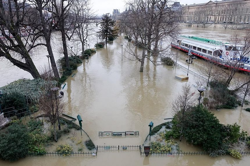 An inundated park in Paris on Tuesday near the Seine River, which rose to about 5m. The river's normal level is about 2m. Left: A resident rowing down a flooded street in the suburb of Villeneuve-Saint-Georges yesterday.