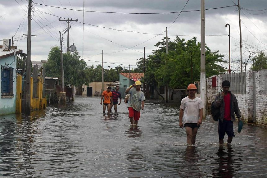 Residents wade along a flooded street in Asuncion after Paraguay river burst its banks due to heavy rains, on Jan 24, 2018.