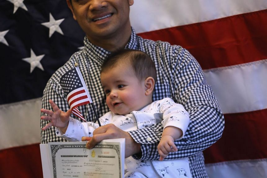Families pose for photos following a US naturalisation ceremony on Jan 22, 2018.