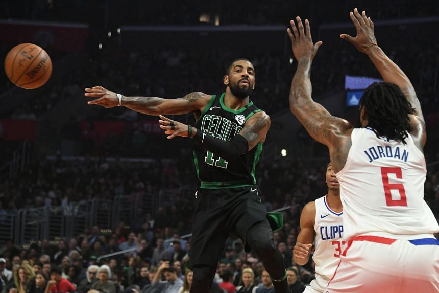 Boston Celtics guard Kyrie Irving passes the ball past LA Clippers centre DeAndre Jordan and LA Clippers forward Blake Griffin during the first half at Staples Center.
