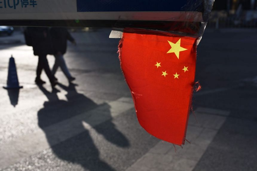 A Chinese national flag hangs from a barrier in a car park in Beijing on Jan 18, 2018.