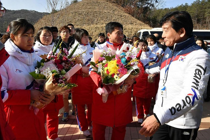The North Korean women's ice hockey team (in white and red) arriving in South Korea's Jincheon yesterday. Athletes from both sides will march under one flag at the opening ceremony of the Pyeongchang Olympics.